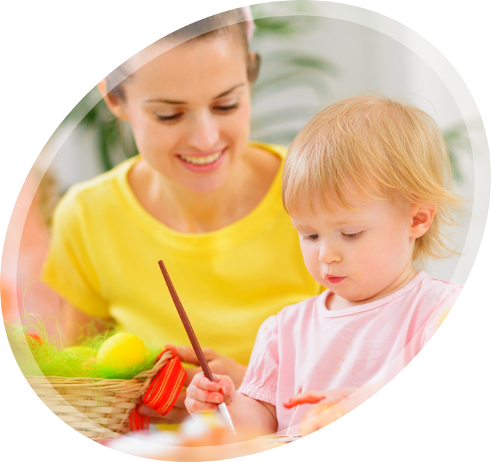 a young girl painting something with her teacher